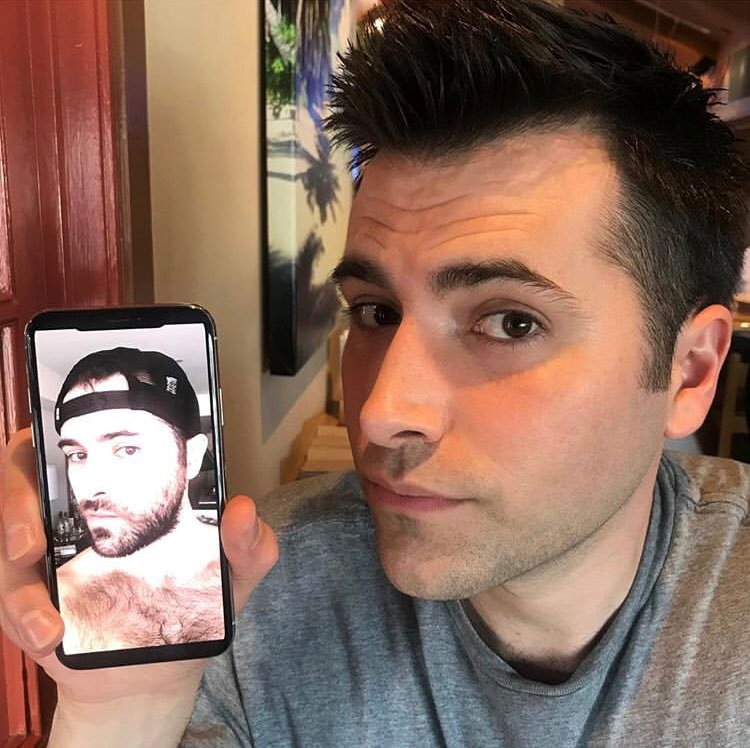 Freddie smith holding phone with beard pic.png
